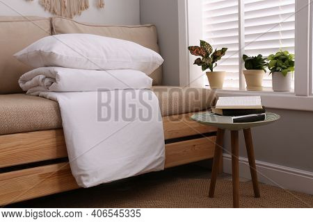 Comfortable Sofa With Blanket Near Window Indoors