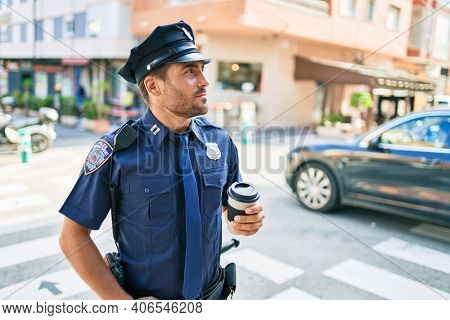 Young hispanic policeman wearing police uniform with serious expression. Drinking cup of take away coffee standing at town street.