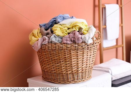Wicker Basket With Dirty Laundry On Washing Machine Near Coral Wall Indoors
