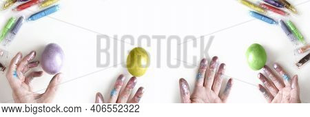 Colored Easter Eggs With Woman Hands On White Background With Mess On Table. Banner Of Macro Moody M
