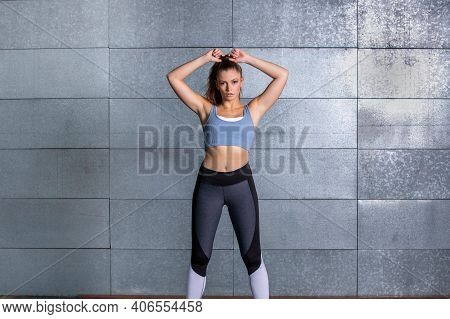 Female Fitness Trainer Standing And Get Ready For Workout And Tie Her Hair In Front Of A Metal Backg