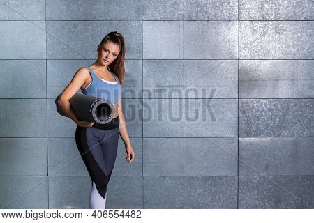 Woman Standing Ready For Fitness Class With A Mat And Sport Outfit In Front Metal Background, Female