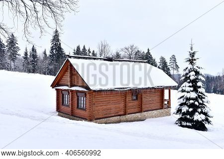 Wooden House In Mountain In Winter Time. Log Cabin In Forest Alone In Wilderness. Wooden House With
