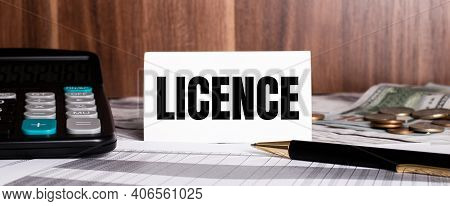 On A Wooden Background Lies A Pen With A Calculator And A White Card With The Word Licence