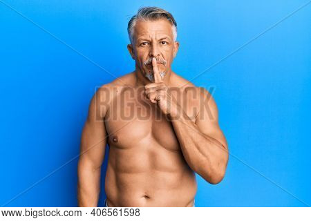 Middle age grey-haired man standing shirtless asking to be quiet with finger on lips. silence and secret concept.