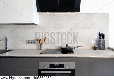 Kitchen With Built In Appliance, Electric Cooker Hood, Stove, Oven And Sink. Frying Pan On Glass Cer
