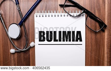The Word Bulimia Is Written On White Paper On A Wooden Background Near A Stethoscope And Black-frame