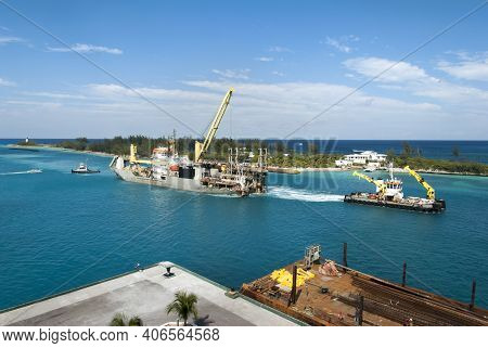 The Aerial View Of A Tugboat Pulling The Large Industrial Ship With A Crane Through Nassau Harbour A