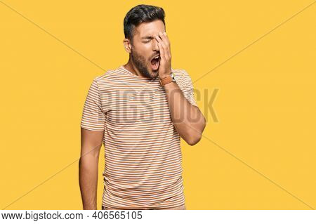 Handsome hispanic man wearing casual clothes yawning tired covering half face, eye and mouth with hand. face hurts in pain.