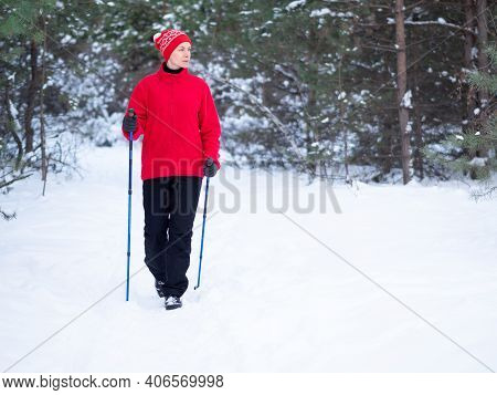 Adult Caucasian Woman In Red Warm Sportwear Does Nordic Walking On The Snow In The Parkland In Winte