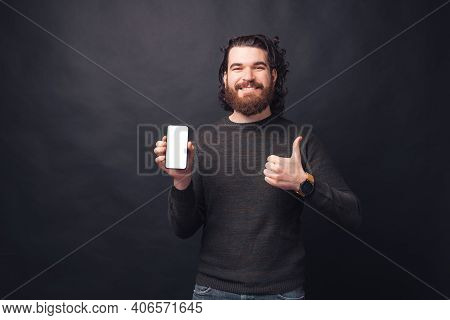 Photo Of Handsome Bearded Man Showing Blank Screen On Mobile Phone And Showing Thumb Up