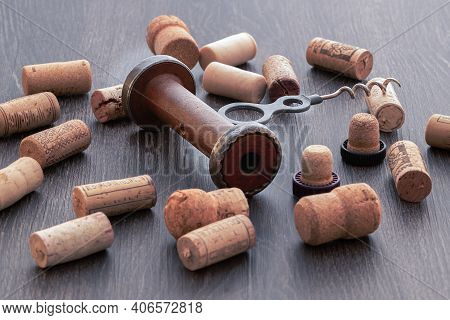 An Old Screw Type Botle Opener And Corks On Top Of The Table.
