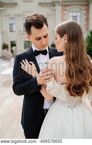 Beautiful, Gentle And Happy Bride And Groom Hugging On Background Of Building