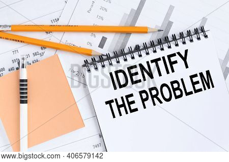 Identify The Problem, Text On White Notepad Paper On A Light Background Near Financial Charts And A