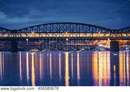 Passenger Train Passing Over Railway Bridge Against City. Cityscape Of Prague At Night, Czech Republ