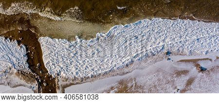 Aerial view over partialy frozen sea with white ice texture
