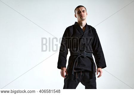 Cool Guy In Black Kimono Fighter Posing In Karate Stance On White Studio Background With Copy Space