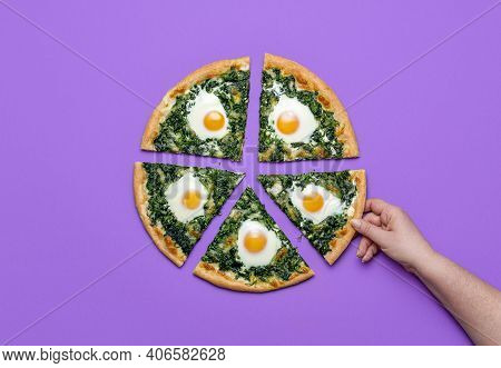 Woman Grabbing A Slice Of Spinach Pizza With Eggs, Isolated On A Purple Background. Top View With Sl