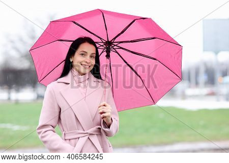 Portrait Of Woman In Coat Who Stands In Rain And Holds Pink Umbrella. Stylish Images For Rainy Autum