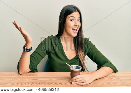 Young brunette woman drinking mate infusion celebrating achievement with happy smile and winner expression with raised hand