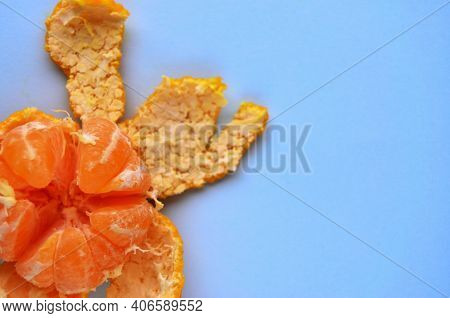 One Fresh Peeled Tangerine In The Open Peel In The Bottom Left Corner On The Table Is Blue With A Co