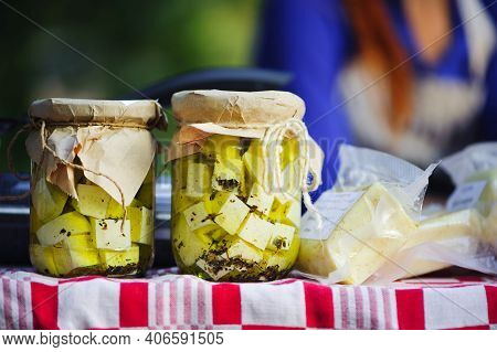 Two Closed Jars Of Feta Cheese Marinated In Oil On A Table With A Blurred Background. Pickled Food,