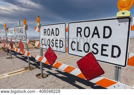 Road closed signs blocking remote Mojave desert highway in scenic Southern California.