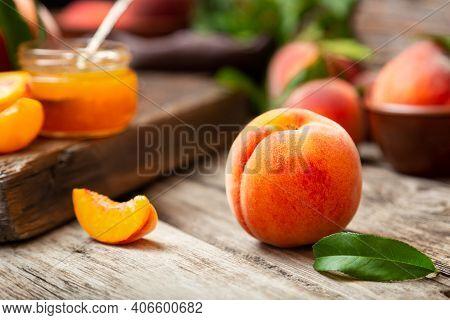 Peach Fruit With Leaf. Ripe Juicy Orange Peach Fruit On Wooden Table. Peach Harvest And Jam On Rusti