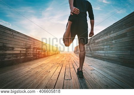 Young Slim Sporty Man Warming And Stretching Legs Before Run Outdoors At Sunset Or Sunrise. Athletic