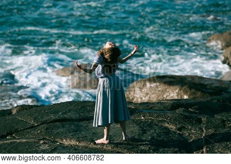 Dancer woman is engaged in choreography on the rocky coast of the ocean.