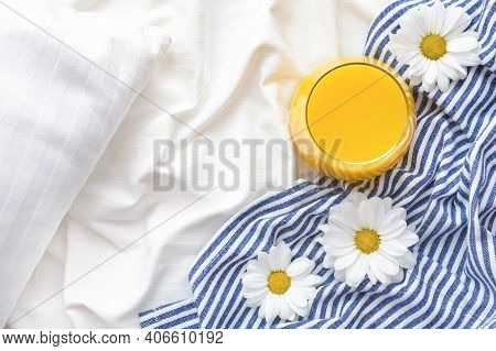 Orange Juice And Chamomile Flowers On Bed With White Linens And Blue Bedspread. Good Morning Concept
