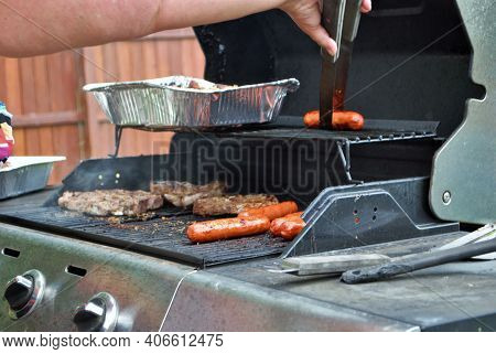Hotdogs And Steak On The Grill At A Backyard Cookout