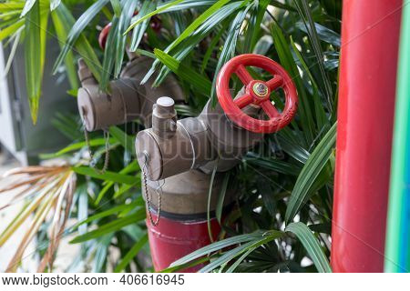 Red Fire Pump In Front Of Concrete Wall. Fire Safety Pump On Cement Floor Of Concrete Building. Delu