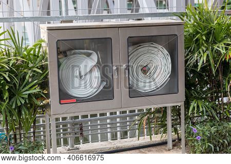 Fire Hose Cabinet. White Hose In The Water Drawer To Extinguish The Fire. Hydrant With Water Hoses A