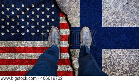 Business Man Stands On Cracked Flags Of Usa And Finland. Political Concept