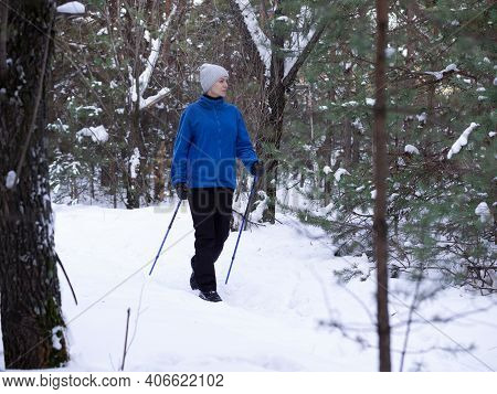 Winter Activity. Adult Caucasian Woman In Blue Warm Sportwear Does Nordic Walking On The Snow In The