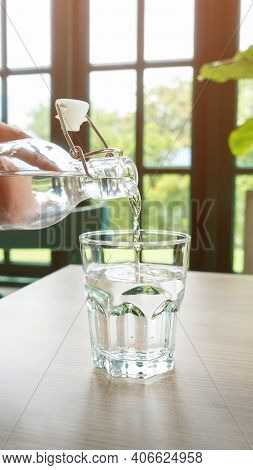 A Glass Of Drinking Water On A Wooden Table.