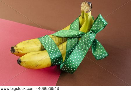 Two Bananas With Green Ribbon, Stock Photo. Ripe Bananas On Brown And Pink Background. Love, Relatio
