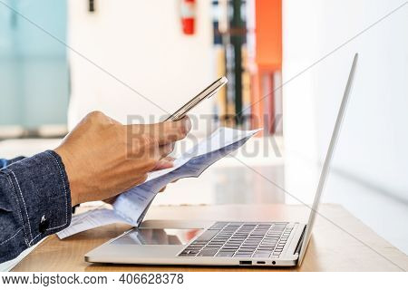 Hands Of Man Using Mobile Smart Phone Payment Online With Family Budget Cost Bills On Desk, Plan Mon