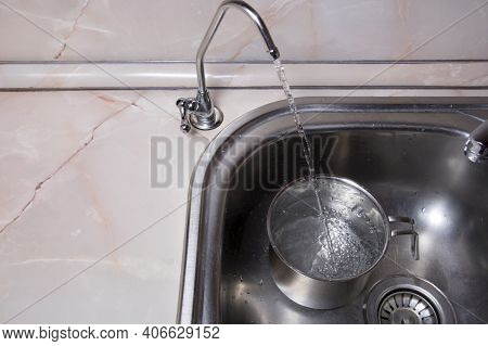 Pouring Filtered Water Into Pot From Water Filter. Closeup Of Sink And Faucet. Drinkable Water In Ki