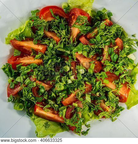 Vegetable Salad Consisting Of Tomato, Lettuce, Parsley, Dill, Onion And Olive Oil. A Platter Of Raw
