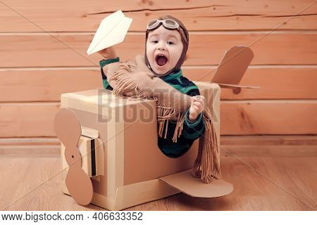 Young Baby Kid Pilot Flying A Cardboard Box On Wooden Background. Child Dream