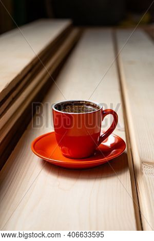 Cup Of Coffee On A Plate In The Workroom Stands On Polished Pine Boards. Business Concept.