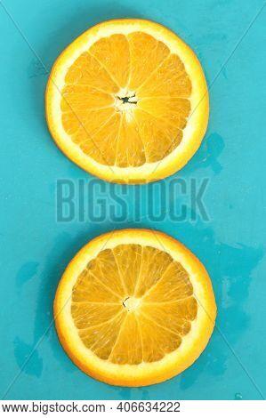 Close Up Of Two Round Orange Citrus Slices On Blue Background, Fresh Summer Mood. Stock Photo Blank