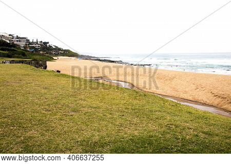 Stretch Of Green Lawn Leading Onto Beach With Residential Buidlings