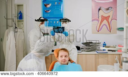Mother And Daughter With Protective Suit Waiting In Clinic Room For Pediatric Dentist To Examining D