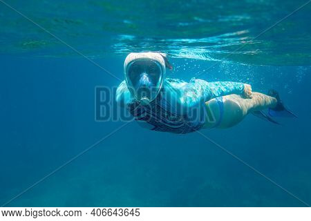 Woman Swimming In Blue Water In Full-face Mask. Young Woman Swimming On Sea Surface. Snorkel In Cora