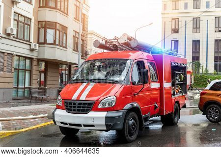 Small Compact Fire Engine Truck With Ladder And Safety Equipment At Accident In Highrise Tower Resid