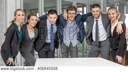 Group Portrait Of Six Business People Team Standing Together In An Office And Cuddle Around Necks To