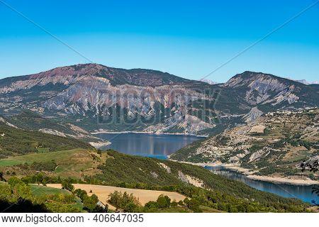 The Village Saint Vincent Les Forts At Lake Serre-poncon. Lac De Serre-poncon Is A Lake In Southeast